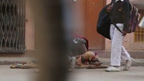 Stående av den gamla tiggaren på gatan i Varanasi, med att förbigå för folk lager videofilmer
