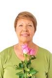 Stående av den gammalare kvinnan med rosa ro Royaltyfria Bilder
