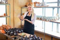 Stående av den glade kvinnakrukmakeriarbetaren med keramisk lerkärl Arkivfoto