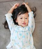 Stående av den gladlynta asiatiska flickan på en soffa royaltyfri fotografi