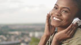 Stående av den gladlynta attraktiva afrikanska kvinnan som ler, sätter på hörlurar och tycker om musiken på det suddigt lager videofilmer