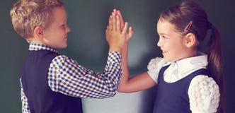Stående av den gladlynta pysen och flickan som tillsammans spelar liten pastejkakaanseende nära svart tavla i klassrumet royaltyfri fotografi