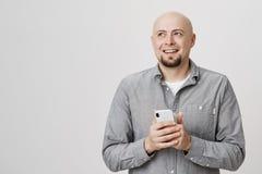 Stående av den gladlynta skalliga caucasian mannen med den hållande smartphonen för skägg, medan återkalla något som är rolig som fotografering för bildbyråer
