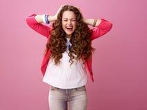 Stående av den gladlynta stilfulla kvinnan som isoleras på rosa färger royaltyfri fotografi