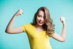 Stående av den gladlynta unga kvinnan som lyfter hennes nävar med att le den gladde framsidan, ja gest royaltyfri foto