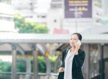 Stående av den gladlynta unga kvinnan som talar på smartphonen och utomhus skrattar härlig aisan affärskvinna som använder mobilt Arkivfoton