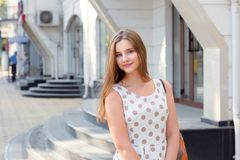 Stående av den gladlynta unga kvinnan som utomhus står och ler arkivbild