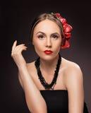 Stående av den glamorösa brunettflickan över mörk bakgrund med bu Arkivfoton