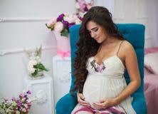 Stående av den gravida härliga brunetten för barn med lockigt hår in Royaltyfri Foto