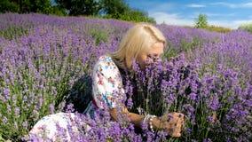 Stående av den gripande gruppen för lycklig romantisk kvinna av blommor och att lukta för lavendel dem Arkivfoto