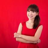 Stående av den gulliga asiatiska kvinnan över röd bakgrund Royaltyfri Bild