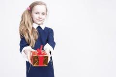 Stående av den gulliga Caucasian blonda ungen med gåvan Mot vita lodisar arkivbilder