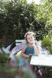 Stående av den gulliga felika flickan på den trädgårds- tabellen Royaltyfria Bilder
