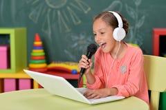 Stående av den gulliga flickan i hörlurar som sjunger karaoke med bärbara datorn arkivfoto