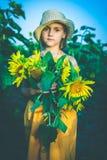 Stående av den gulliga flickan i solrosfält Arkivfoto