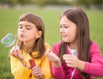 Stående av den gulliga flickan som blåser såpbubblor Arkivfoto