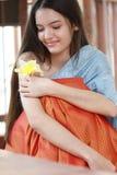 Stående av den gulliga flickan som luktar blomman i hennes hand royaltyfria bilder