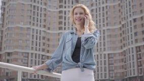 Stående av den gulliga le säkra blonda kvinnan som framme talar vid mobiltelefonen av skyskrapan stads- livsstil Kvinnlig stad arkivfilmer