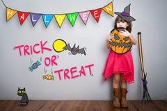 Stående av den gulliga lilla flickan med halloween dräktgarnering t Royaltyfri Foto