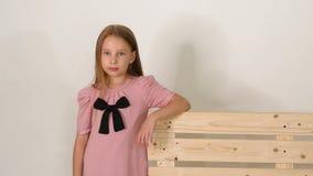 Stående av den gulliga lilla flickan nära bänk i studio på vit bakgrund stock video