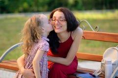 Stående av den gulliga lilla flickan som kysser hennes unga moder i Eyesglasses och röd klänning Lyckligt familjsammanträde på bä Fotografering för Bildbyråer