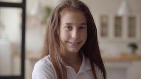Stående av den gulliga lilla flickan som ser kameran som lyckligt ler Carefree barndom Liten emotionell flicka hemma verkligt arkivfilmer