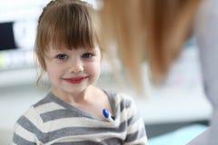 Stående av den gulliga lilla flickan som sitter på doktorskontoret med termometern arkivfoto