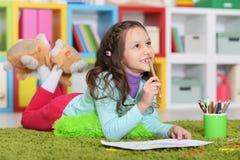 Stående av den gulliga liten flickateckningen, medan ligga royaltyfri bild