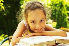 stående av den gulliga lockiga skolaflickan som utanför läser en gammal bok Royaltyfri Bild