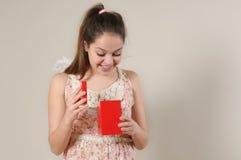 Stående av den gulliga lyckliga öppnande hennes valentin för ängel flickan gi för dag Royaltyfria Bilder