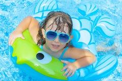 Stående av den gulliga lyckliga lilla flickan som har gyckel i simbassäng som svävar i den rubber cirkeln för blå uppfriskande va arkivbild