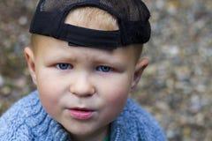 Stående av den gulliga pojken i ett lock royaltyfri foto