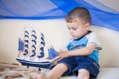 Stående av den gulliga pysen med skeppet i hans händer Den lilla sjömannen spelar i hans rum Nautiskt begrepp arkivbild