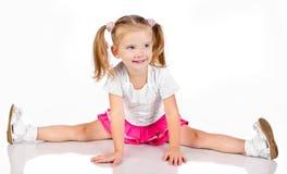 Stående av den gulliga sittande le liten flicka arkivfoto