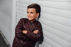Stående av den gulliga trendiga pojken framme av träväggen royaltyfria bilder