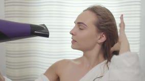 Stående av den gulliga unga caucasian kvinnan som ser kameran och dansar, medan torka hennes hår med hårtorken n?tt stock video