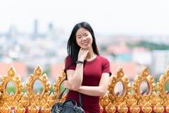 Stående av den gulliga unga enkla ögonlockkvinnan, mot på pagod av buddhismtemplet i ferie fotografering för bildbyråer