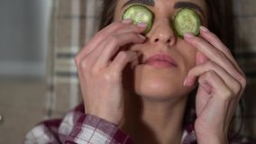 Stående av den gulliga unga kvinnan i pajamaen som gör ögonmaskeringen från gurkor, i hemtrevlig afton, att kyla och att koppla a arkivfilmer