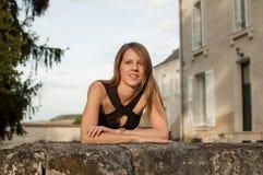 Stående av den gulliga unga kvinnan med långt skenhåranseende på slottbakgrund under sommartid arkivbilder