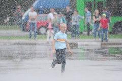 Stående av den gulliga ungepojken som spelar med springbrunnen på gatan på en solig dag Barn som har roligt utomhus arkivfoto