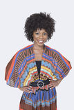 Stående av den härliga afrikansk amerikankvinnan i traditionella kläder som står över grå bakgrund Arkivfoton