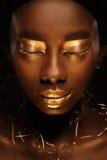 """Stående av den härliga afrikanska kvinnan med idérik guld- make†""""upp och smycken Fotografering för Bildbyråer"""