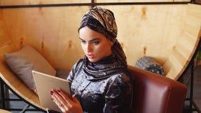 Stående av den härliga arabiska muslimska flickan som använder minnestavlan stock video