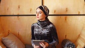 Stående av den härliga arabiska muslimska flickan som använder minnestavlan arkivfilmer