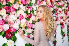 Stående av den härliga blonda kvinnan i klänning över färgrika blommor royaltyfria foton