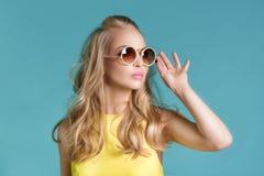 Stående av den härliga blonda kvinnan i solglasögon och gul skjorta på blå bakgrund carefree sommar royaltyfri bild