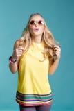 Stående av den härliga blonda kvinnan i solglasögon och gul skjorta på blå bakgrund carefree sommar royaltyfri fotografi