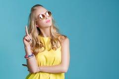 Stående av den härliga blonda kvinnan i solglasögon och gul skjorta på blå bakgrund carefree sommar arkivbild