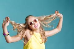 Stående av den härliga blonda kvinnan i solglasögon och gul skjorta på blå bakgrund carefree sommar royaltyfria foton