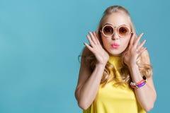 Stående av den härliga blonda kvinnan i solglasögon och gul skjorta på blå bakgrund carefree sommar royaltyfria bilder